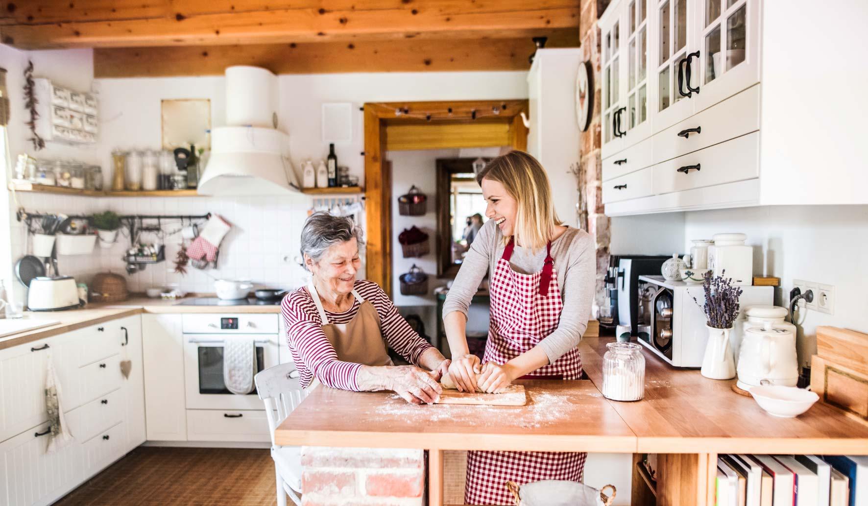 Une accueillante familial entrain de faire la cuisine avec une personne âgée.