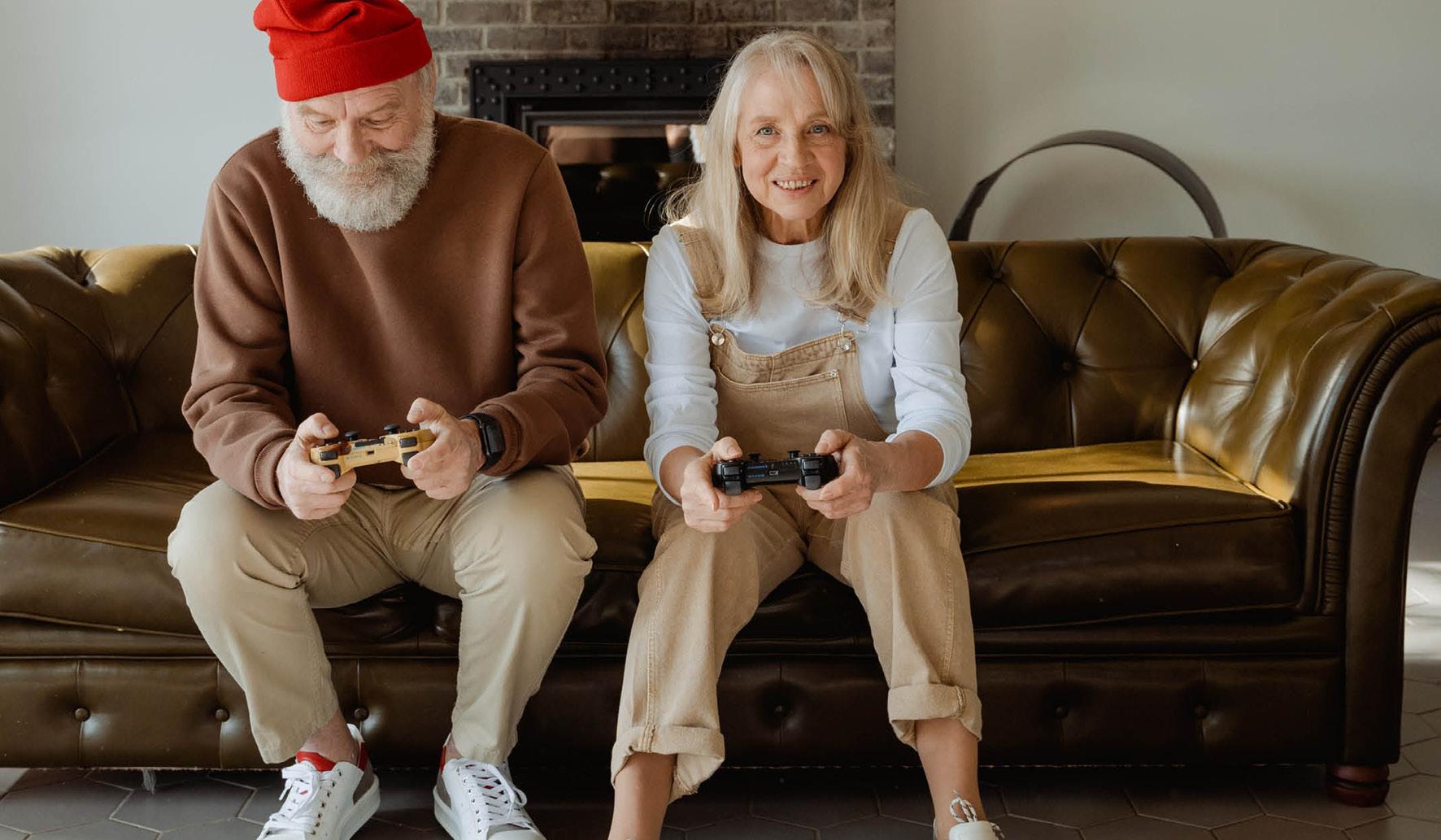 Deux personnes âgées jouent à la console à leur domicile.