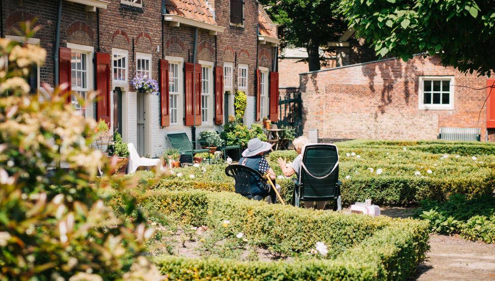 Des personnes âgées sont au soleil dans le jardin d'un accueillant familial.