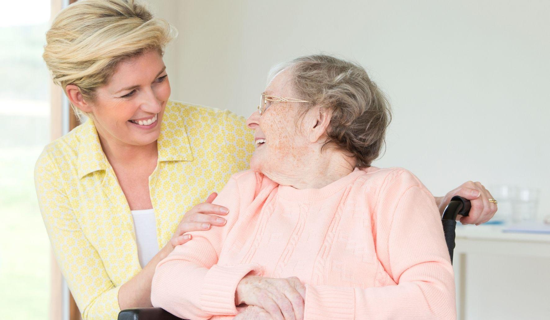 Une auxiliaire de vie sociale avec une dame âgée en fauteuil roulant.