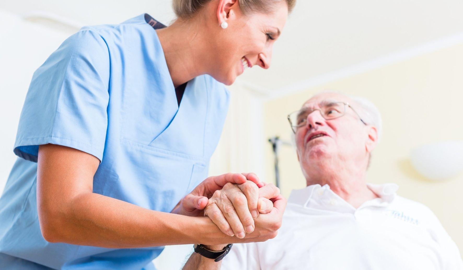 Une aide soignante qui tient la main d'un homme âgé